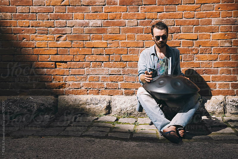 Musician playing handpan in front of the wall by T-REX & Flower for Stocksy United