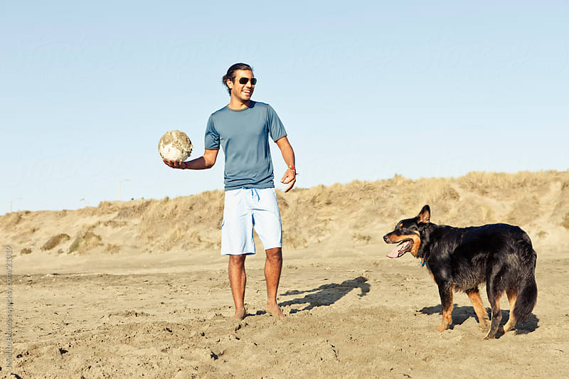 Hispanic Young Man and His Dog at the Beach Playing Catch Ball by Joselito Briones for Stocksy United