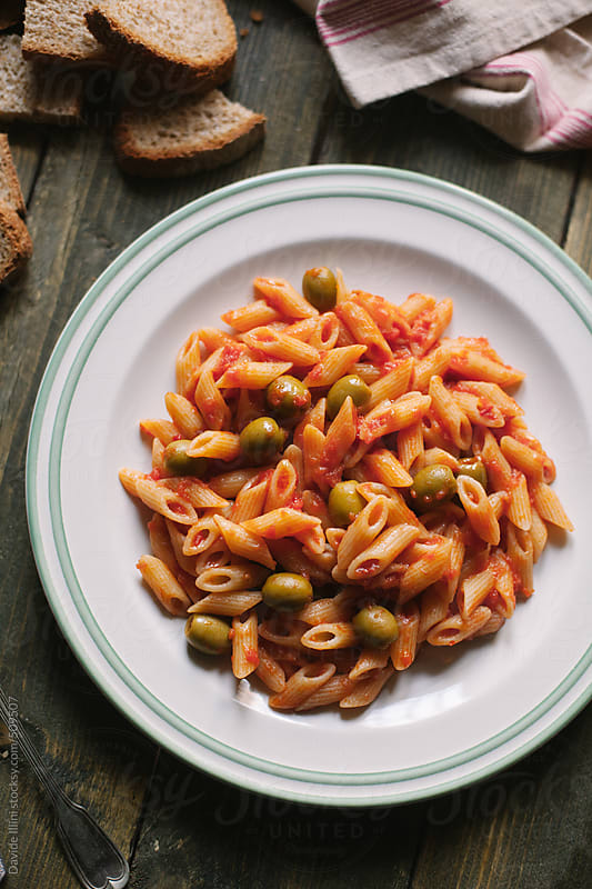 Pasta with tomato sauce and olives by Davide Illini for Stocksy United