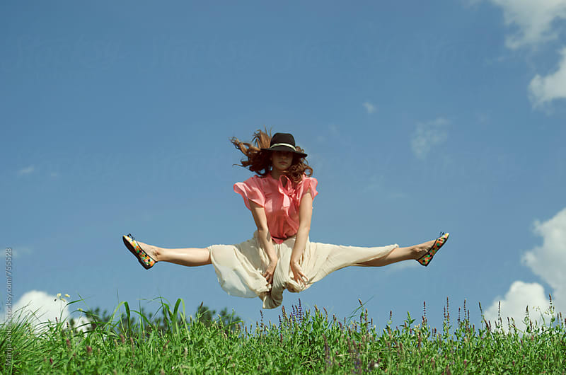 Girl jumping on the sunny meadow by Marija Anicic for Stocksy United