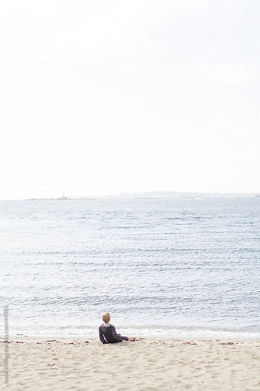 Boy sitting by the sea  by Jonas Räfling for Stocksy United