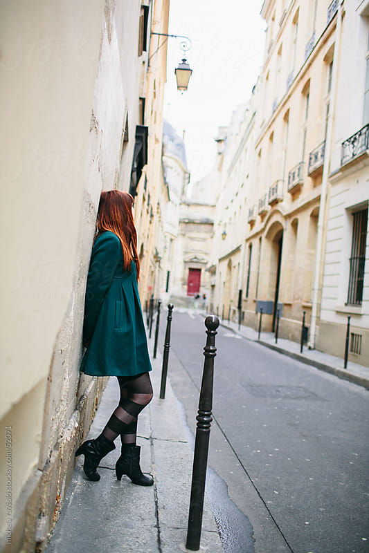 Young woman leaning to wall by michela ravasio for Stocksy United