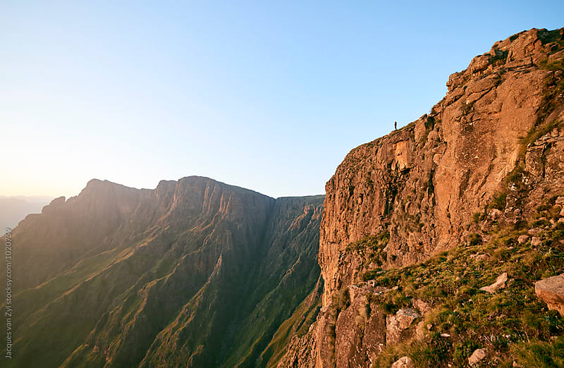 Hiker standing on a mountain cliff edge at sunrise. by Jacques van Zyl for Stocksy United
