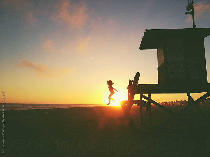 young girl silhouette jumping off lifeguard stand at beach at sunset  by Kristin Rogers Photography for Stocksy United