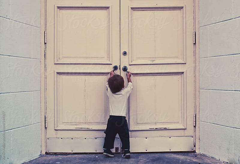 Toddler Boy Trying to Open Double Doors by Kevin Keller for Stocksy United