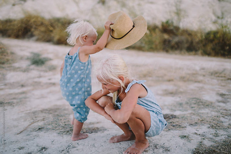 Little baby girl playing with her elder sister and the hat  by Evgenij Yulkin for Stocksy United