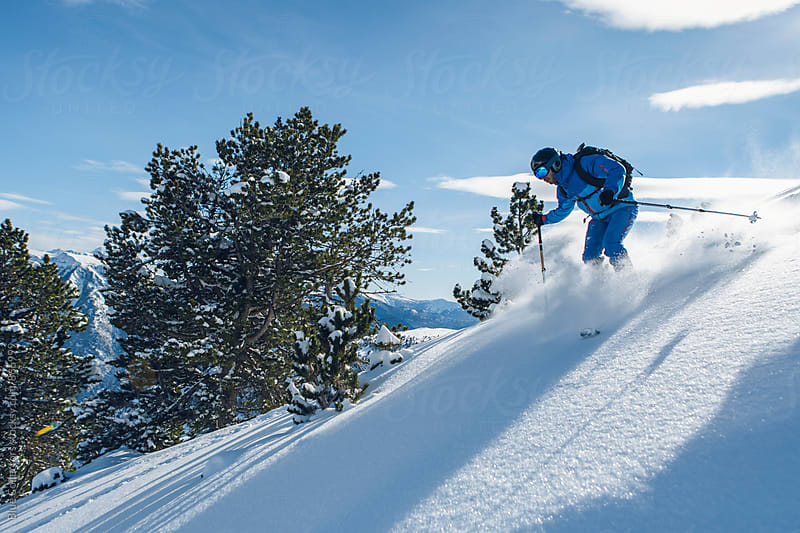 Skier man down the powder mountain in a sunny day by Jordi Rulló for Stocksy United