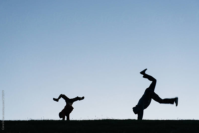 Father and son attempt handstands outside at sunset by Cara Dolan for Stocksy United