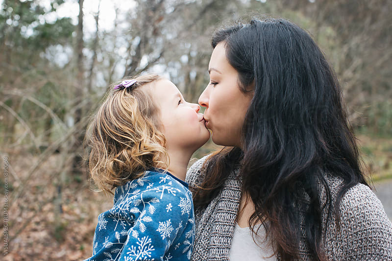 Outdoor Portrait of Small Daughter Kissing Her Mother  by Julien L. Balmer for Stocksy United
