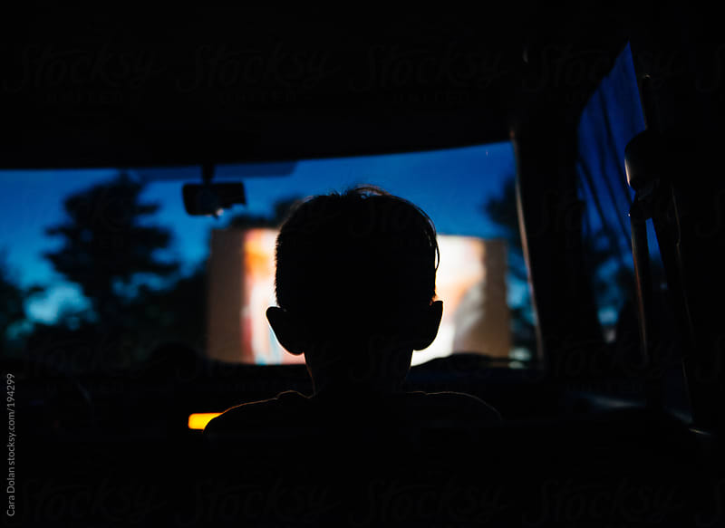 Child sits in the car watching a movie at a drive-in movie theater by Cara Dolan for Stocksy United