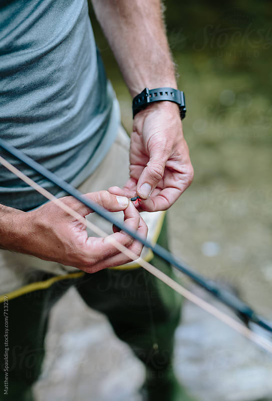 Close up of hands tying fly to fishing line by Matthew Spaulding for Stocksy United