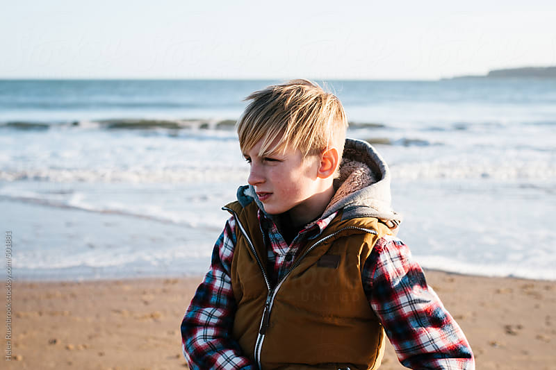 A teenage boy on a beach, looking away from camera. by Helen Rushbrook for Stocksy United