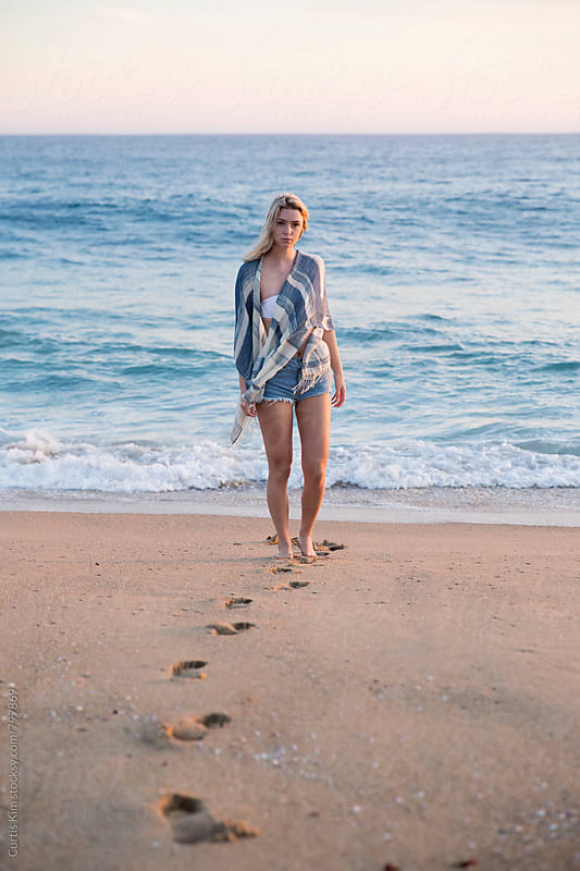 Blonde female walking on the beach by Curtis Kim for Stocksy United