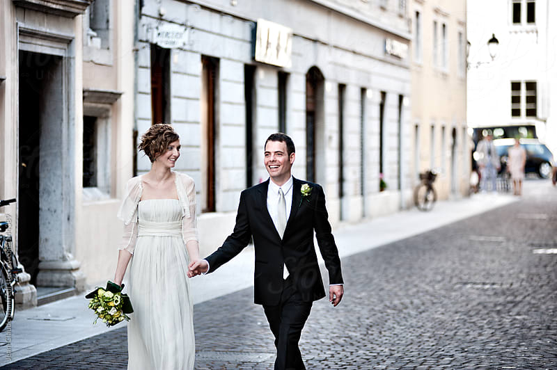 Young wedding couple walking on the city by Jean-Claude Manfredi for Stocksy United