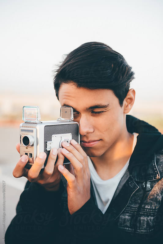 Young male going analog with vintage movie camera by Emmanuel Hidalgo for Stocksy United