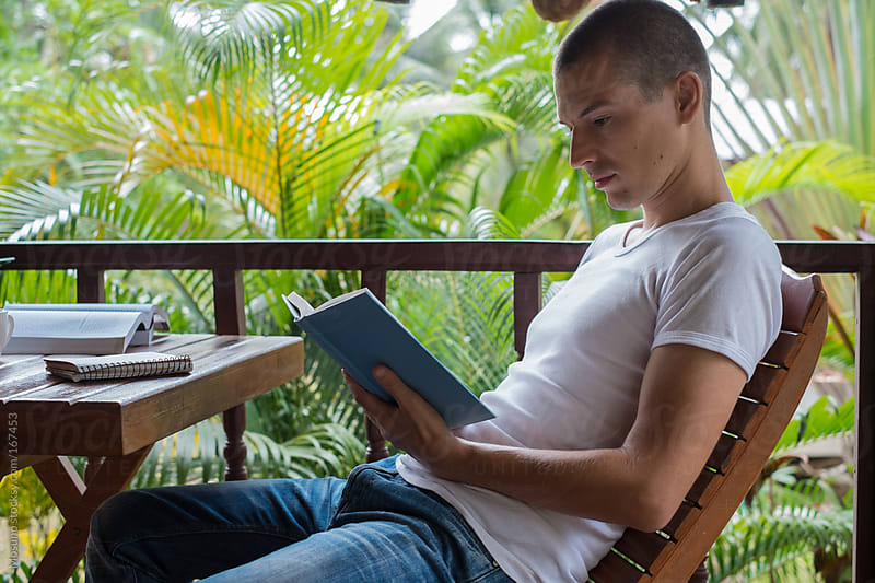 Man Reading a Book on a Tropical Balcony by Mosuno for Stocksy United