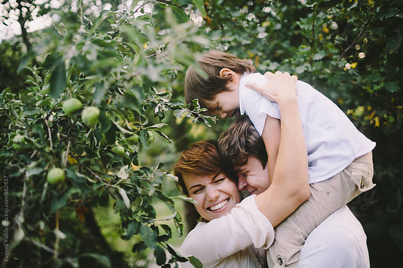 Family under the apple tree by Evgenij Yulkin for Stocksy United