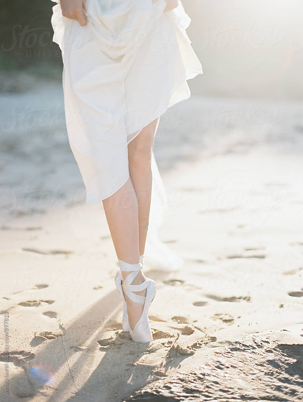 ballet pointe shoes with wedding gown on sand beach in sunlgiht by wendy laurel for Stocksy United