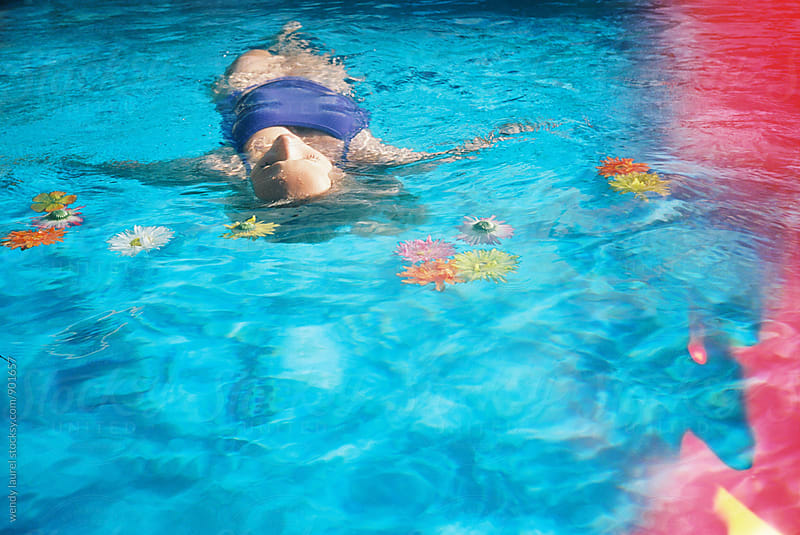 girl floating in pool with light leak effect on film by wendy laurel for Stocksy United
