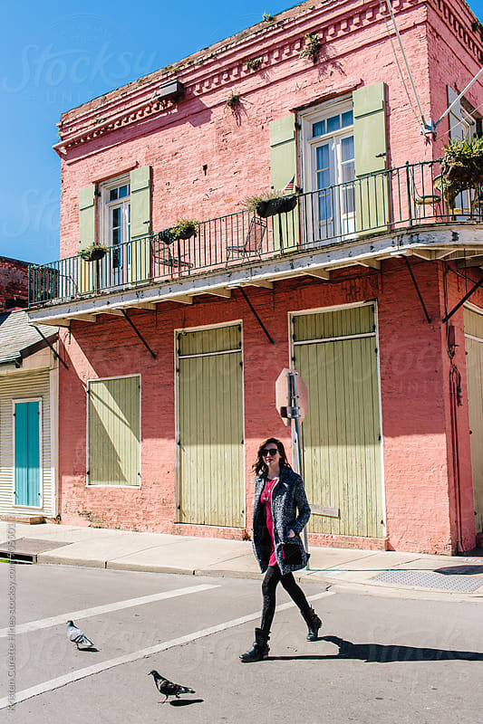 A woman tourist walking across the street in the French Quarter, New Orleans by Kristen Curette Hines for Stocksy United
