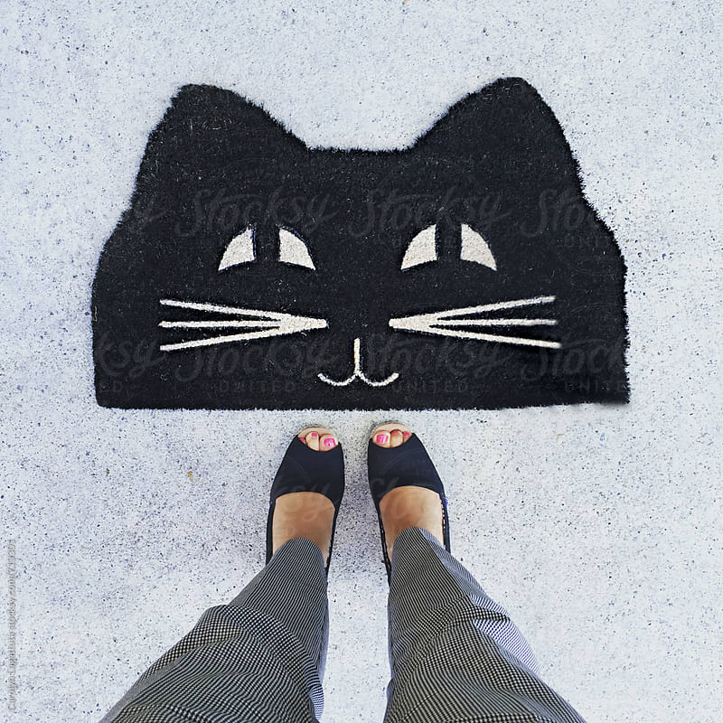 Female standing above a cute doormat of a black cat's face by Carolyn Lagattuta for Stocksy United