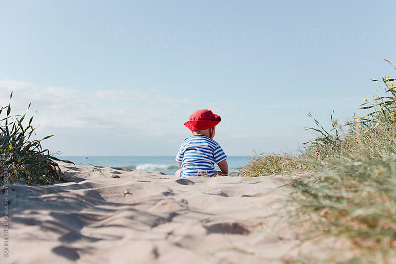 Baby sitting on the sand watching the sea. Beautiful landscape. by BONNINSTUDIO for Stocksy United