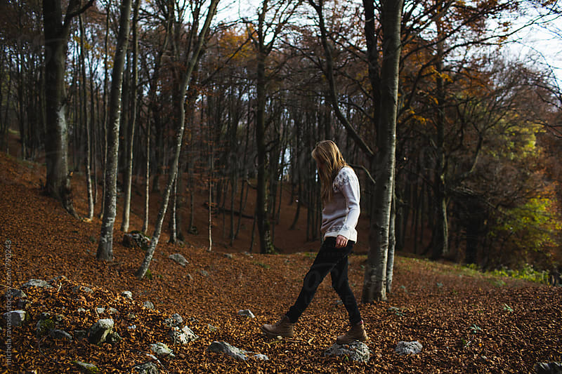 Young woman walking on the stones in the woods by michela ravasio for Stocksy United