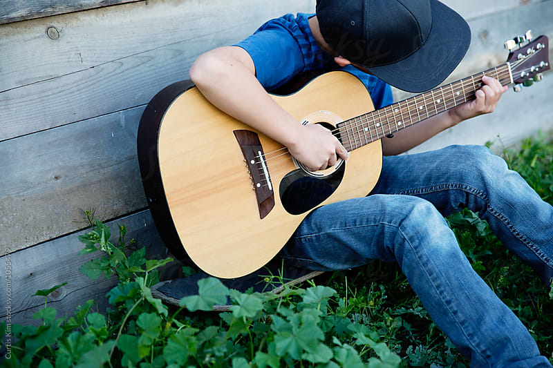Boy playing his guitar in nature by Curtis Kim for Stocksy United