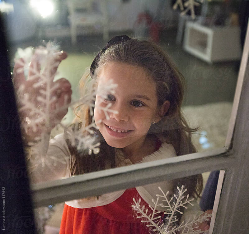 Girl Decorating Windows for Christmas  by Lumina for Stocksy United