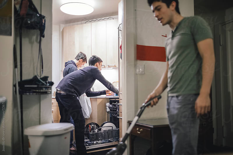 Young Student Roommates Helping Each Other Clean Their Apartment by Joselito Briones for Stocksy United