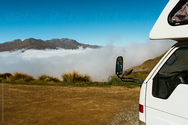 A very low cloud between mountains seen from the side of a vehicle by Leandro Crespi for Stocksy United