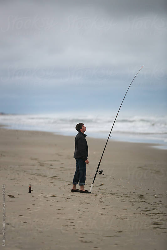 Man waiting and surf fishing with long rod and beer on beach by Matthew Spaulding for Stocksy United