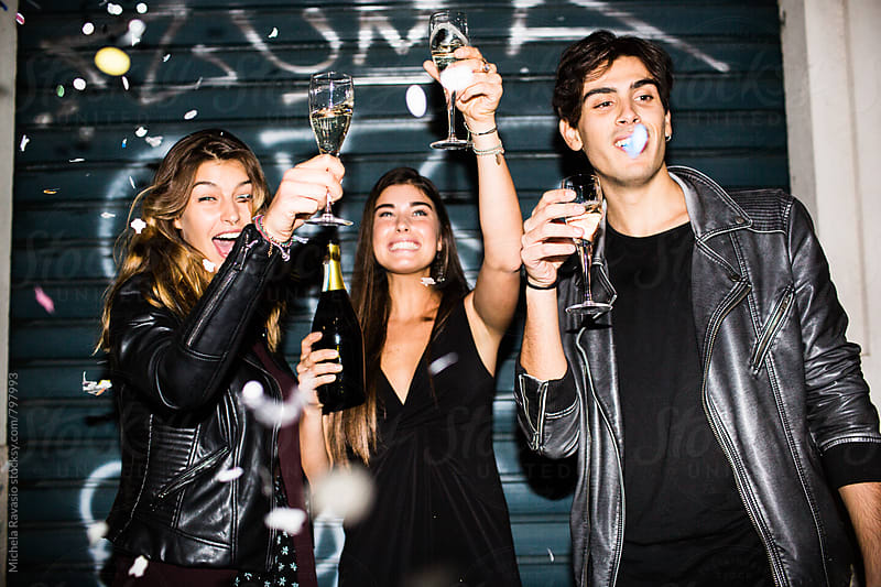 Happy friends toasting together with champagne by michela ravasio for Stocksy United
