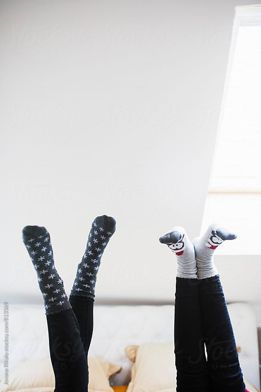 Two female friends wearing Christmas socks by Jovana Rikalo for Stocksy United