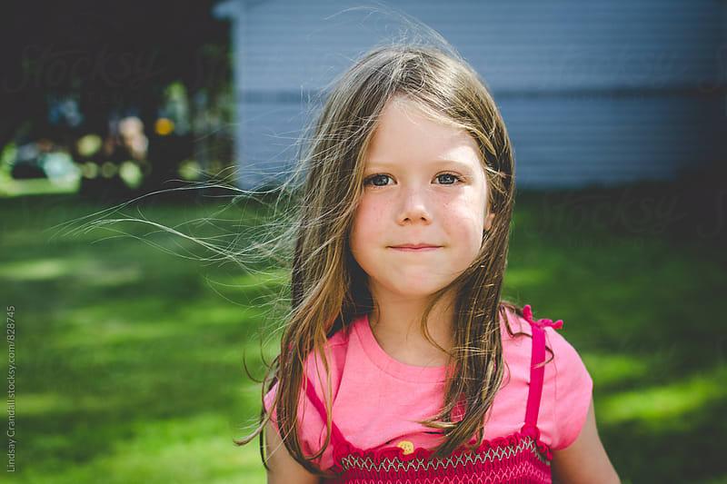 Child standing in backyard in summertime by Lindsay Crandall for Stocksy United
