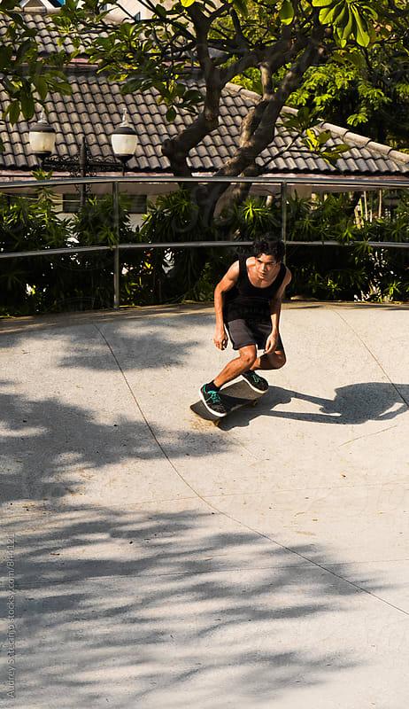 Young skateboarder in skate park driving his skateboard by Audrey Shtecinjo for Stocksy United
