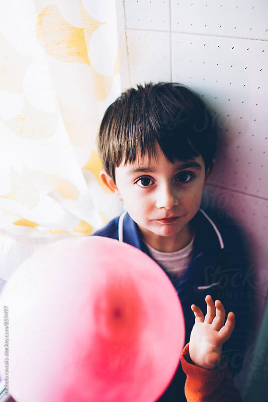 Children playing with a pink balloon by michela ravasio for Stocksy United