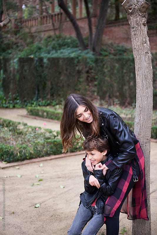 Sister hugging her little brother and smiling by Guille Faingold for Stocksy United