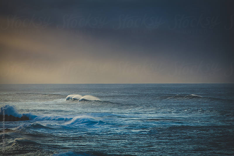 A lone wave shining at sunset by Christian Tisdale for Stocksy United
