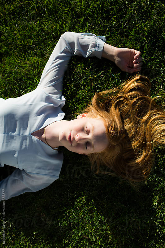 Redhead girl relaxing on a green grass by michela ravasio for Stocksy United