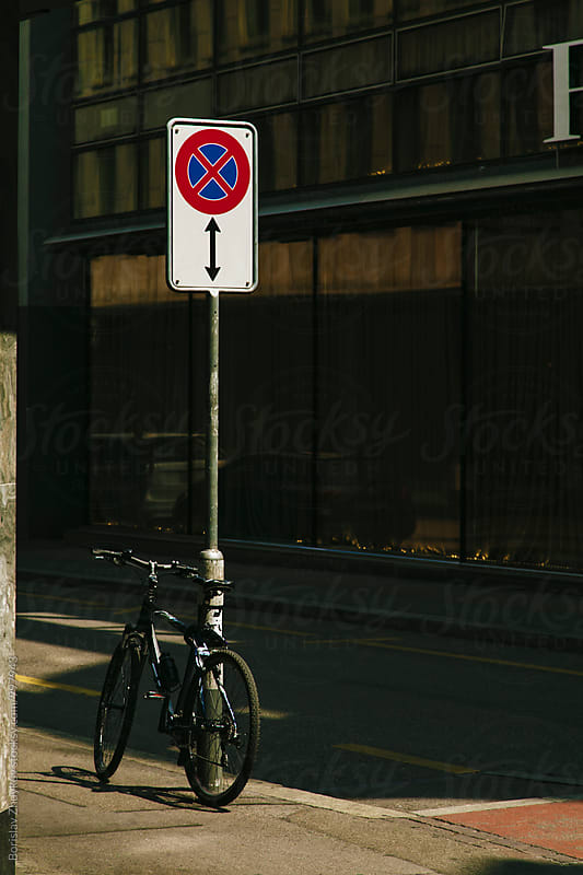 Bicycle leaning against street sign - stopping and parking prohibited  by Borislav Zhuykov for Stocksy United