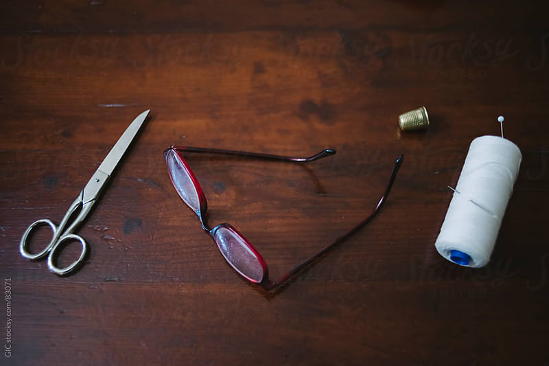 Old scissors, glasses and sewing thread by GIC for Stocksy United