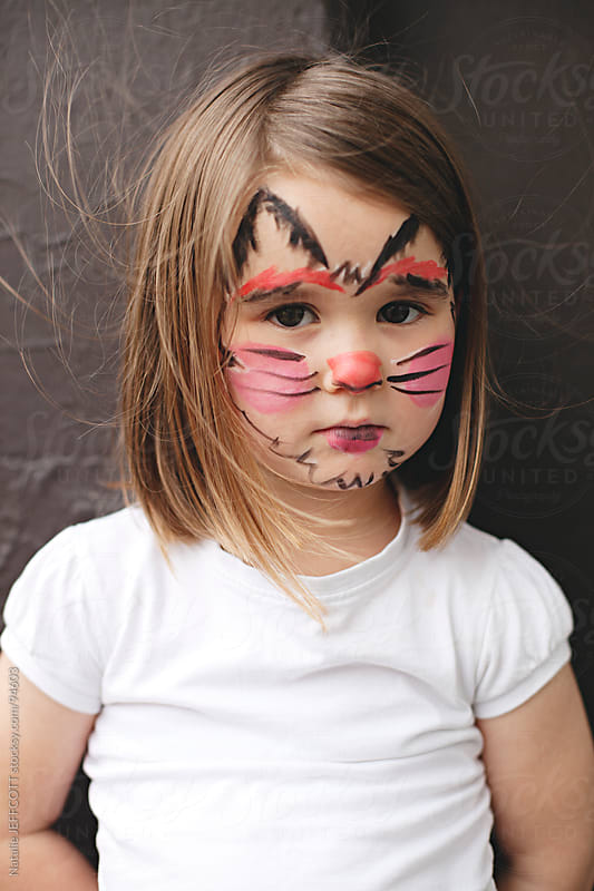 young girl with face painted as black cat for Halloween by Natalie JEFFCOTT for Stocksy United