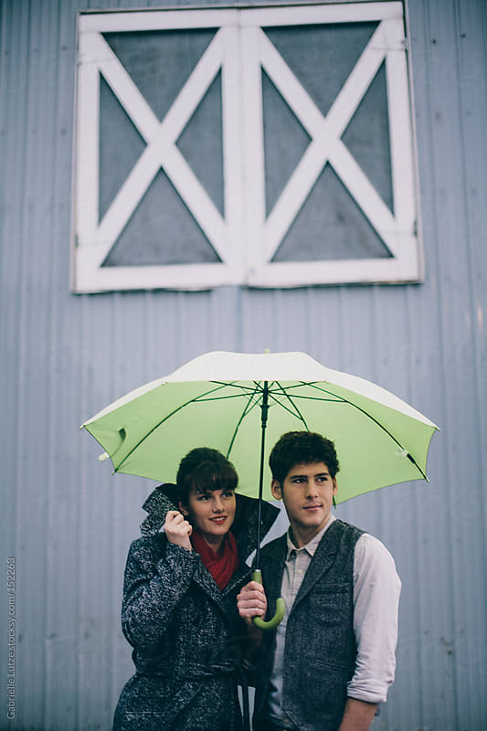 Couple together in the Rain by Gabrielle Lutze for Stocksy United