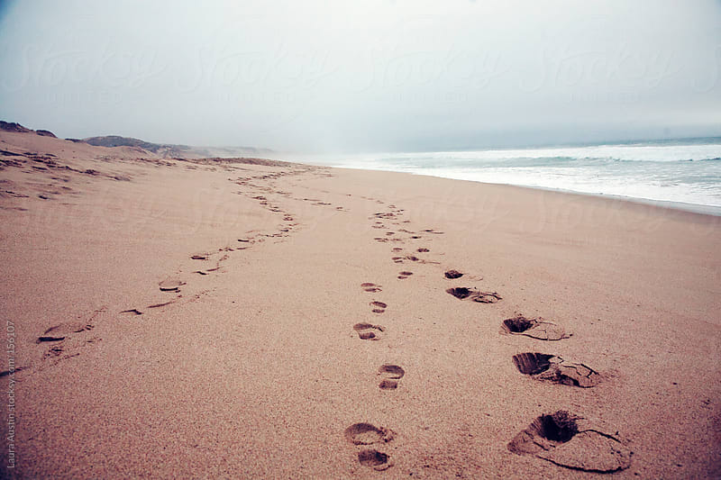 Footprints in the sand leading down a beach by Laura Austin for Stocksy United