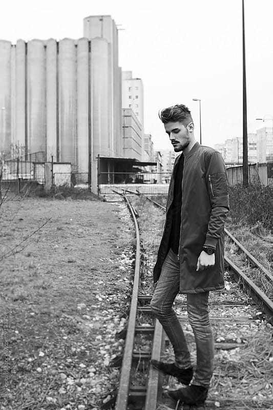 Young man in a coat walking on the streets by Maja Topcagic for Stocksy United