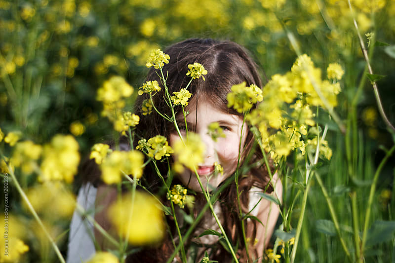 Cute little girl is hiding behind yellow flowers by Jovana Rikalo for Stocksy United