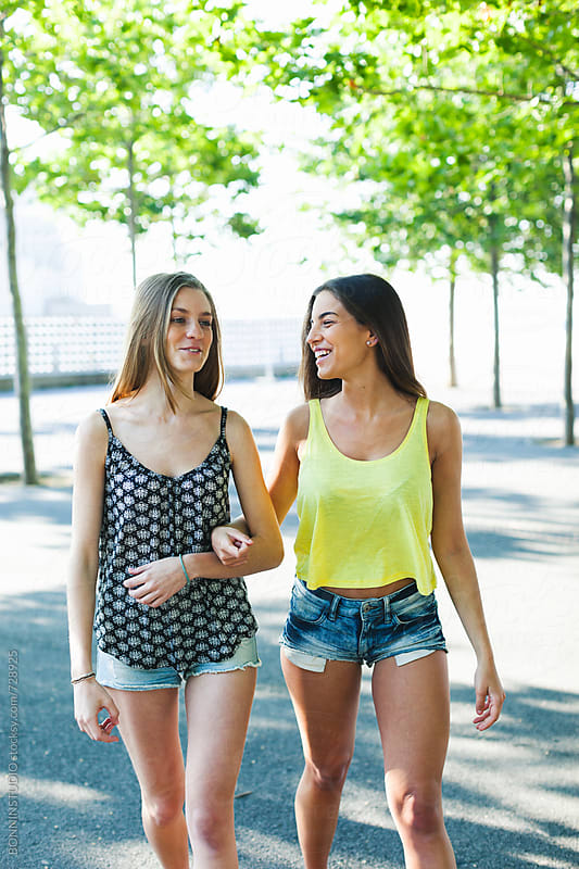 Young female friends walking together in the park. by BONNINSTUDIO for Stocksy United