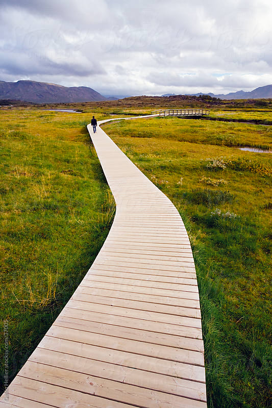 Boardwalk meandering towards rugged cliffs and stormy sky at Thingvellir National Park near Reykjavik, Iceland, Polar Regions by Gavin Hellier for Stocksy United