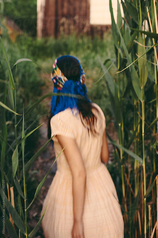 Young woman from behind walking  trough reed . by Aleksandra Kovac for Stocksy United